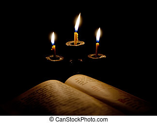 old Psalter and candles in candelabrum. Focus on andelabrum