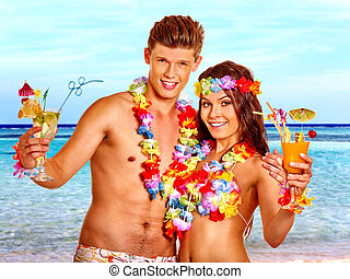 Couple with cocktail at Hawaii wreath beach. Guy holding...