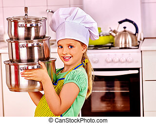 Child cooking at kitchen. - Child wearing hat and apron...