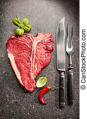Raw fresh meat T-bone steak and seasoning on dark background