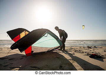 Kitesurfer prepating his equipment on a beautiful sunset at...