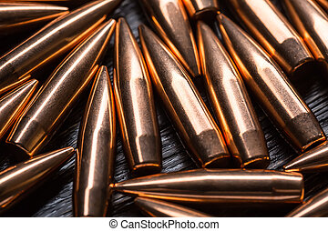 Placer copper bullets on a dark wooden background, shot in...