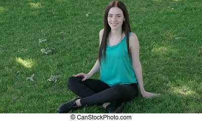 Female sitting with crossed legs on the green grass - Woman...