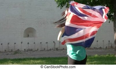 Happy women with Union Jack flag dancing outdoors in sun...