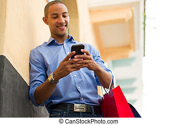 African American Man Text Messaging On Phone With Shopping...