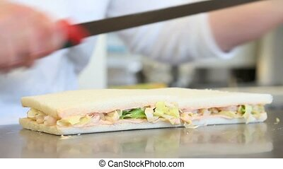 Hands cutting sandwich with shrimp and lettuce