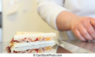 hands prepare sandwich on the tray