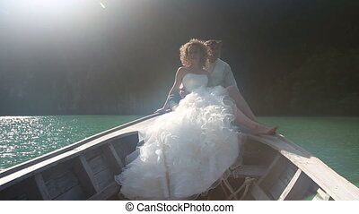 groom embraces bride sitting in longtail boat - smile groom...