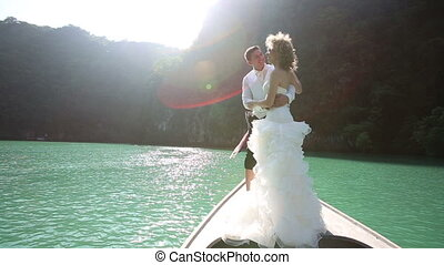 wedding couple standing on longtail boat - curly blonde...