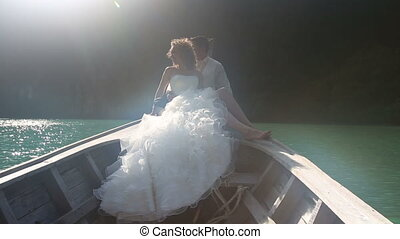 groom embraces bride sitting in longtail boat - blonde bride...