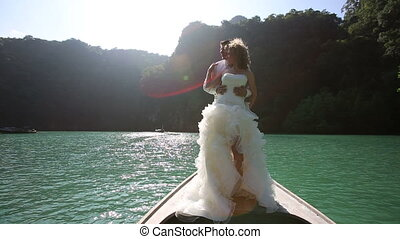 wedding couple standing on longtail boat - wind blows up...