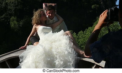 photographer shoots by video camera bride and groom kiss -...