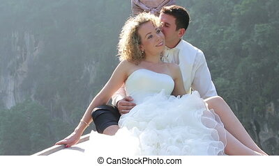 groom embraces bride sitting in longtail boat - strong...