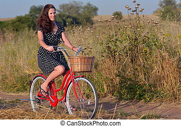 Young woman riding vintage bicycle - Young woman wearing a...