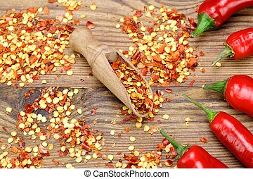 Hot Chili Peppers, Milled Peppers Flakes On Wooden Board -...