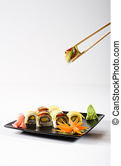 sushi on a plate with chopsticks picking up one piece