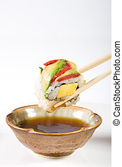 dipping sushi in sauce - chopsticks dipping a colorful piece...