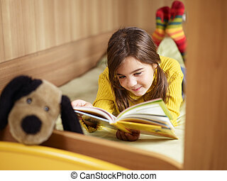 girl reading book - girl lying on bed and reading book. Copy...