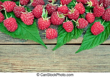 Many Ripe Raspberries With Leafs On The Old Wood Background