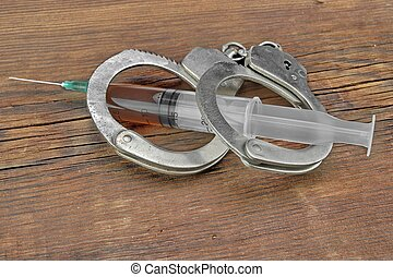 Syringe and Handcuffs On Grunge Wood Background - Syringe...
