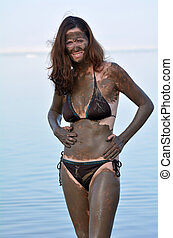 Woman enjoying the natural mineral mud sourced from the Dead Sea Israel