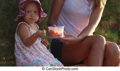 small child eats fruits with fork out of lunch box which...