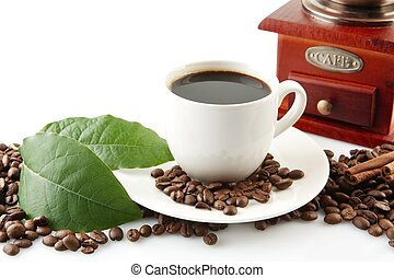 Scattered coffee beans with cups of coffee and leaf -...