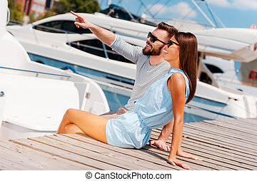 There is our yacht Joyful young couple smiling and looking...