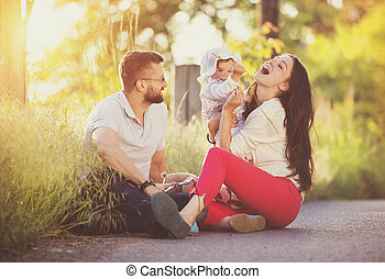 Happy family - Happy young family having fun outside in...
