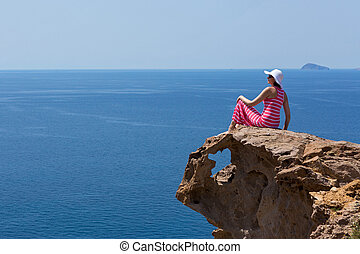 Woman in a long dress sitting on a rock on the sea - Young...