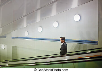 Descending on escalator - Young businessman standing on...