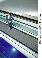 Moving upstairs - Elegant businessman with briefcase moving...