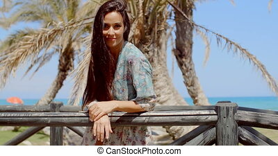 Pretty Young Woman Leaning on Railing at the Beach - Young...