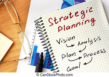 Notepad with  Strategic planning concept on a wooden board.