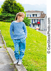 Fashion portrait of a pretty little girl of 7 years old, wearing blue knitted pullover, jeans and boots