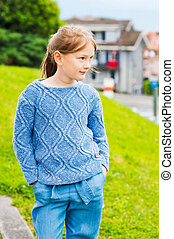 Fashion portrait of a pretty little girl of 7 years old, wearing blue knitted pullover, jeans with belt