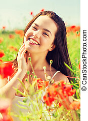 smiling young woman on poppy field - happiness, nature,...
