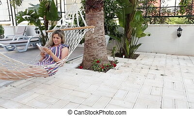 Lady reading the book in the hammock near pool - Lady...