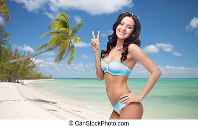 happy woman in swimsuit showing victory hand sign - people,...