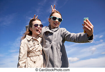 happy girls with smartphone taking selfie outdoors - people,...