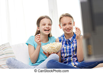 happy girls with popcorn watching tv at home - people,...