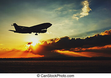 Silhouette of an airplane landing Beautiful sunset evening...