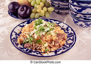 Traditional uzbek meal called pilaf and onion in vintage...