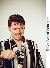Smile man in bathrobe brushing teeth - Laughing man in...