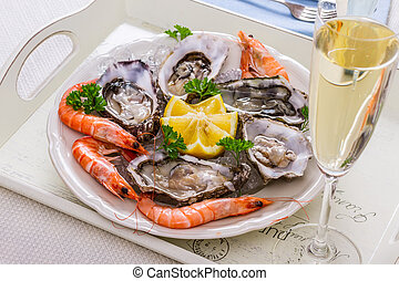 Champagne glass, oysters shell with shrimp on serving tray,...