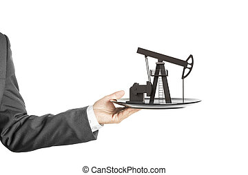 Oil pump on the plate in hand isolated on white
