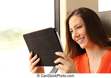 Passenger woman reading a tablet or ebook in a train - Happy...