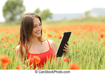 Woman reading ebook in a red field - Woman reading an ebook...