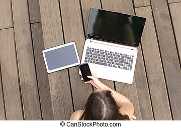 Woman using multiple devices phone laptop and tablet lying...