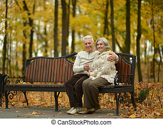 Happy senior couple relaxing in autumn park